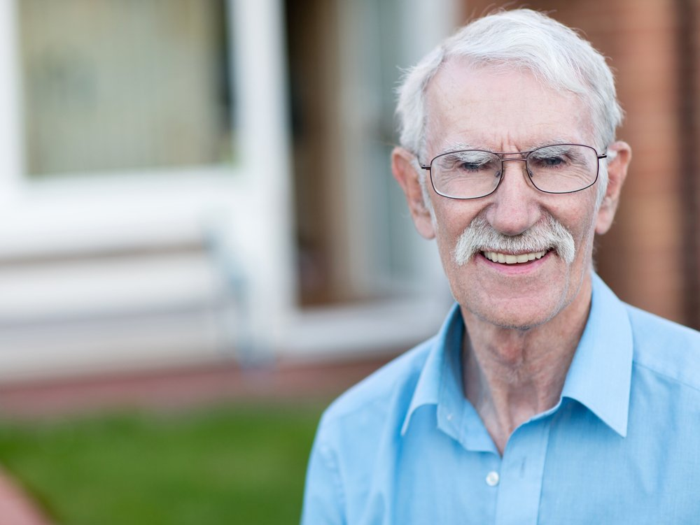 Retired man smiling outside his house